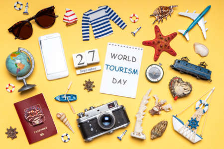 Happy world tourism day. Touristic objects, smartphone, passport, camera, sunglasses and decorative items on light background. Flat lay. Calendar date September 27, notebook, text WORLD TOURISM DAY