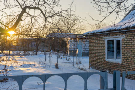 Empty suburban plot covered with snow and left for the winter brick cottage house in wintery evening at sunset. Russian dacha concept.