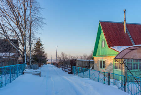 Street in country village covered with snow and left for the winter brick cottage house on wintery evening at sunset. Russian dacha concept. Standard-Bild