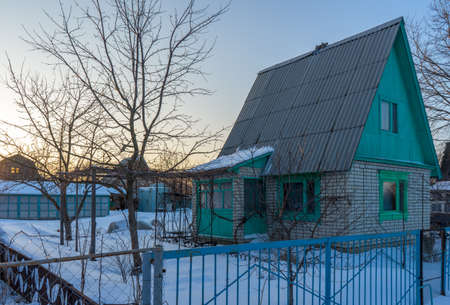 Empty suburban plot covered with snow and left for the winter brick cottage house on wintery evening at sunset. Russian dacha concept.