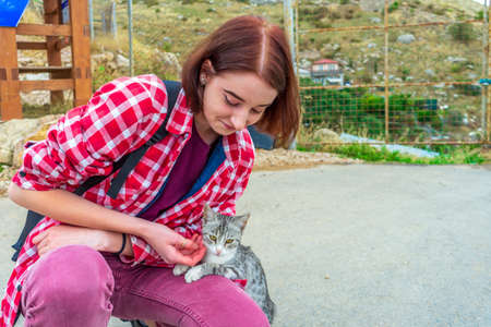 Teen volunteer girl with little cat in small town. Young tourist and cute abandoned hungry kitten. Authentic lifestyle moments. Pets protection concept.
