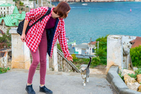 Teen volunteer girl with little cat in small coastal town. Young tourist calling cute abandoned hungry kitten. Authentic lifestyle moments. Pets protection concept.