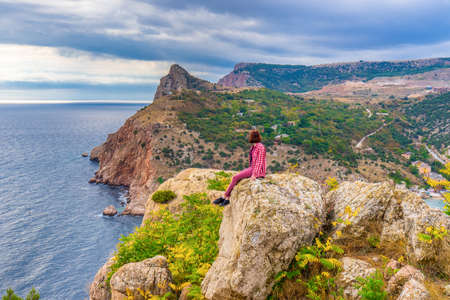 Teen tourist girl sitting on mountain cliff against beautiful seascape in cloudy day. Young lady relaxing on background of sea, mountains and sky. Traveling and discovering distant places of Earth. Standard-Bild