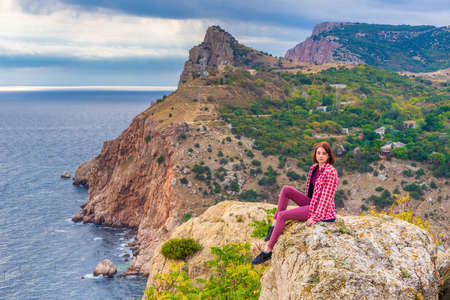 Teen tourist girl sitting on mountain cliff against beautiful seascape in cloudy day. Young lady posing on background of sea, mountains and sky. Traveling and discovering distant places of Earth. Standard-Bild