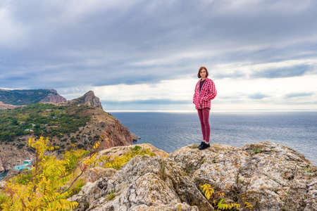 Teen tourist girl standing on mountain cliff against beautiful seascape in cloudy day. Young lady posing on background of sea, mountains and sky. Traveling and discovering distant places of Earth.