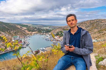 Handsome middle aged tourist man sitting on stone against beautiful landscape of small coastal town in cloudy day. Man in casual clothes using smartphone on background of hills, sea, sky and township. Standard-Bild