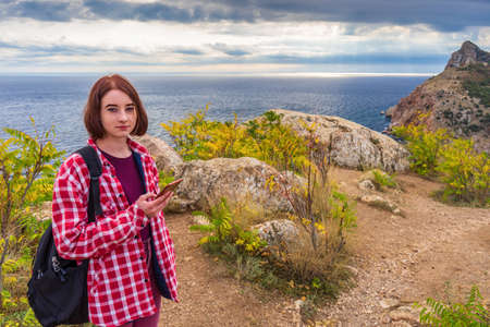 Teen tourist girl with smartphone standing against beautiful seascape in cloudy day. Young lady posing on background of sea, mountains and sky. Traveling and discovering distant places of Earth.