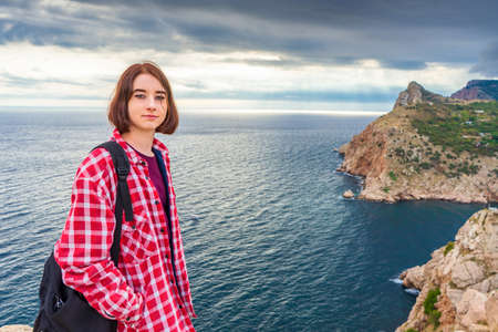 Teen tourist girl with backpack standing against beautiful seascape in cloudy day. Young lady posing on background of sea, mountains and sky. Traveling and discovering distant places of Earth.