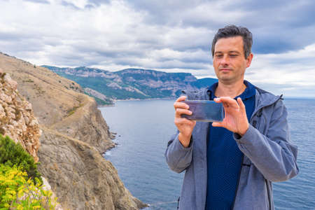 Handsome middle aged tourist man standing against beautiful seascape in cloudy day. Man using smartphone on background of sea, mountains and sky. Traveling and discovering distant places of Earth.
