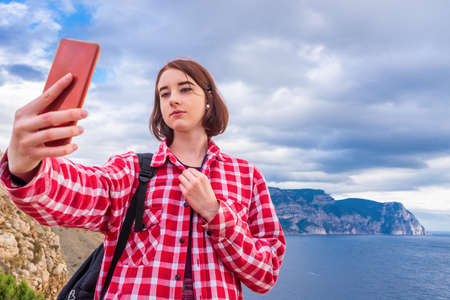 Teen tourist girl taking selfie with smartphone against beautiful seascape in cloudy day. Young lady posing on background of sea, mountains and sky. Traveling and discovering distant places of Earth. Standard-Bild