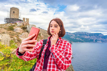 Teen tourist girl taking selfie with smartphone against seascape and ruined fortress. Young lady posing on background of sea, mountains and landmark. Traveling, discovering distant places of Earth Standard-Bild