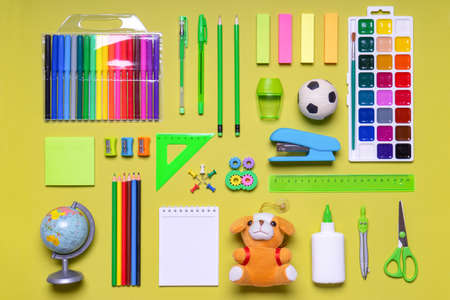 Back to school. Office supplies and goods for creativity on yellow green pastel background. Kids school items, toys and stationery. Education concept.