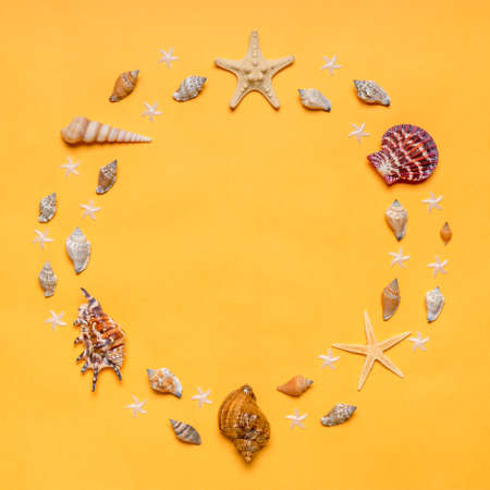 Frame made of decorative seashells and sea stars on bright yellow background. Summer vacation concept. Flat lay, top view, space for text.