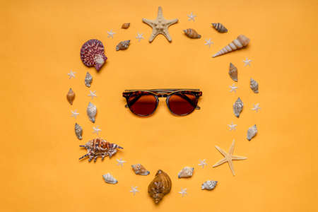 Frame made of decorative seashells and sea stars and sunglasses on bright yellow background. Creative composition in minimal style. Summer vacation concept. Flat lay, top view.