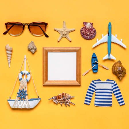 Various decorative nautical items, plane, sailboat and sunglasses on bright yellow background. Empty wooden photoframe, mock up. Sea travel, summer vacation at ocean concept. Standard-Bild