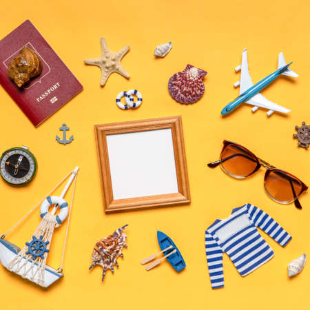 Various decorative nautical items, plane, sailboat, sunglasses, passport and compass on bright yellow background. Empty wooden photoframe, mock up. Sea travel, summer vacation at ocean concept. Standard-Bild