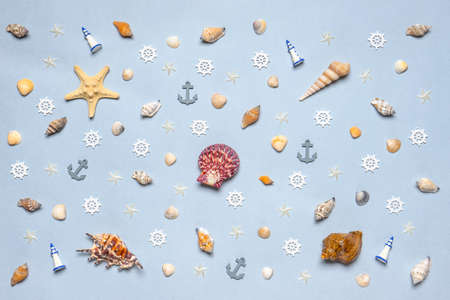 Various decorative nautical items, seashells, sea stars and miniature toys on blue pastel background. Sea travel, summer vacation at ocean concept. Flat lay, top view.