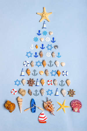 Christmas tree made of various seashells, sea stars, decorative items and miniature toys: lighthouses, life buoys, steering wheels, anchors, vessels. New year holidays at sea or ocean concept.