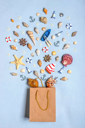Various decorative nautical items, seashells, sea stars and miniature toys flying from kraft paper bag on blue pastel background. Sea travel, summer vacation at ocean concept. Flat lay, top view.