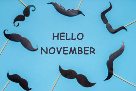 Various black photo booth props mustaches of different shape on blue background. Text HELLO NOVEMBER, men's health awareness month campaign concept. Flat lay.
