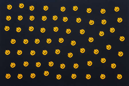 Halloween background. Orange confetti pumpkins on black paper background. Happy Halloween concept. Greeting card, festive backdrop for Halloween or Thanksgiving holiday. Flat lay, top view.