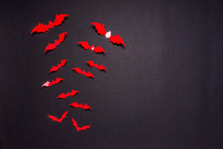Halloween composition. Flock of red bats on black background. Happy halloween, trick or treat party concept. Flat lay, top view, copy space. Standard-Bild