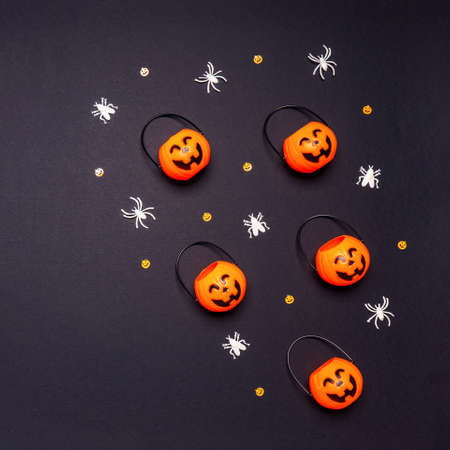 Halloween composition. Pumpkin baskets with flies and spiders on black background. Happy halloween, trick or treat party concept. Flat lay, top view, copy space.
