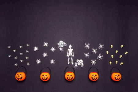 Halloween composition. Pumpkin baskets with skeletons, flies and spiders on black background. Happy halloween, trick or treat party concept. Flat lay, top view, copy space. Standard-Bild