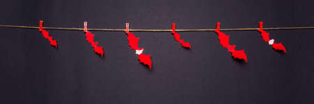 Halloween composition. Red bats hanging on rope by clothespins on black background. Happy halloween, trick or treat party concept. Flat lay, top view, banner.
