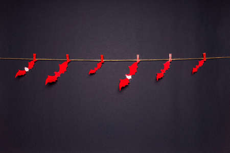 Halloween composition. Red bats hanging on rope by clothespins on black background. Happy halloween, trick or treat party concept. Flat lay, top view, copy space. Standard-Bild