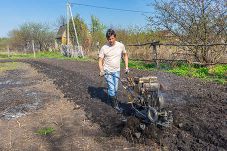 Man in wellingtons with cultivator plows ground in sunny day. Land cultivation, soil tillage. Spring work in garden. Gardening concept. Фото со стока