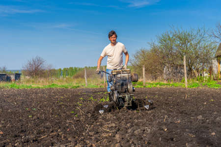 Man in wellingtons with cultivator plowing ground in sunny day. Farmer plowing kitchen-garden in suburb. Land cultivation, soil tillage. Spring work in garden. Gardening concept. Фото со стока