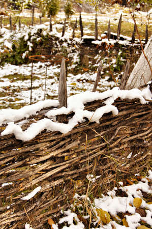 ethnographical: Autumn time: rural view with very old fence with yellow leaves and snow