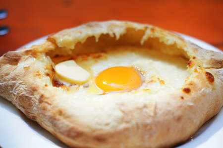 Ajarian or Adjaruli khachapuri, filled with cheese and topped with a raw egg and butter - traditional dish of georgian cuisine Stock Photo