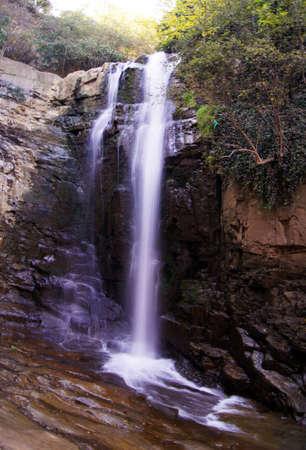 Grande cascade forêt tropicale, des rayons de soleil, et des rochers moussus Banque d'images