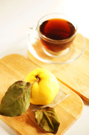 Cup of tea and quince fruit on the wooden desk photo
