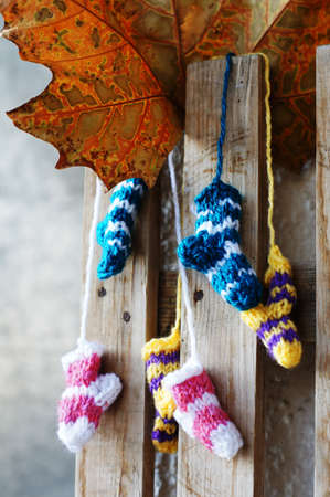 acrylic yarn: Small knitten socks on the wooden background Stock Photo