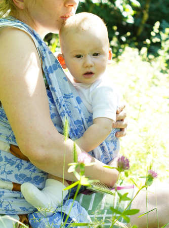 Nice woman with her baby boy in a sling baby carrier photo