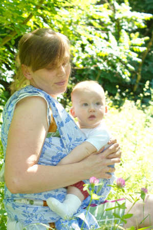 physiologic: Nice woman with her baby boy in a sling baby carrier Stock Photo
