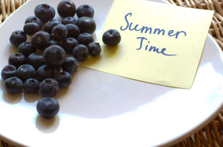 Fresh picked organic blueberries in a white plate on a woven basket slate background