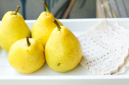 Natural pear juice in a glass bottle and fresh pears on the table