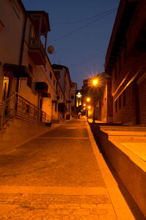 lightup: Narrow street of Old Tbilisi with light-up minaret in the night