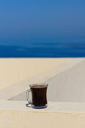 fredo: Cappello di paglia e la tazza di caffè sul tetto con vista sul mare Egeo Archivio Fotografico