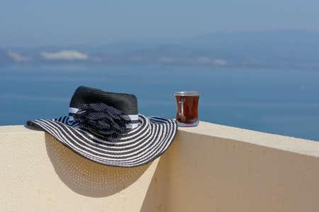 fredo: Cappello di paglia e la tazza di caff� sul tetto con vista sul mare Egeo Archivio Fotografico
