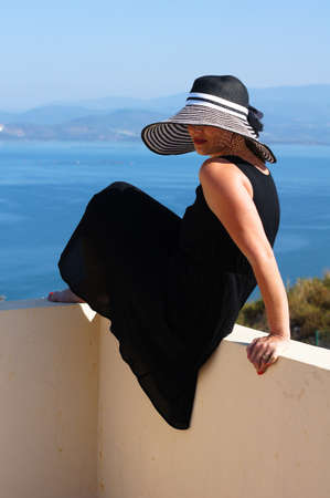 Beautiful woman in a straw hat on the villa photo