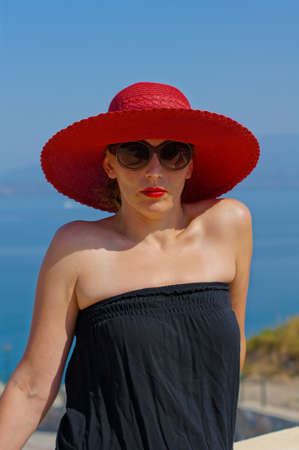 Beautiful woman in a straw hat on the villa's roof with view to Aegean sea photo