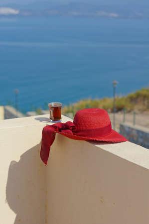 fredo: Cappello di paglia e tazza di caff� sul tetto con vista sul mare Egeo
