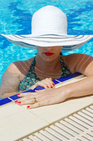 beautiful girl in a hat relaxing near a swimming pool photo