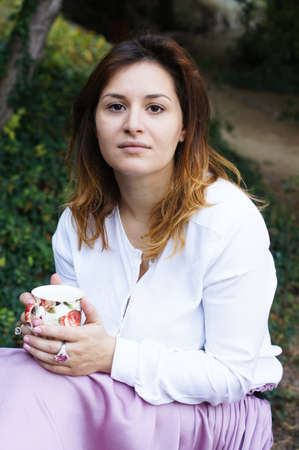 Portrait of beautiful young woman drinking tea outdoor photo