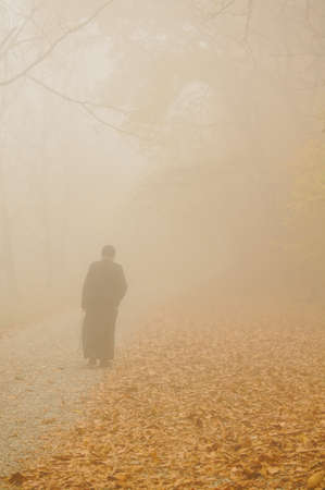 Monk in the foggy autumnal forest photo